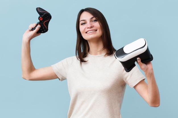 Mulher sorridente segurando fone de ouvido de realidade virtual