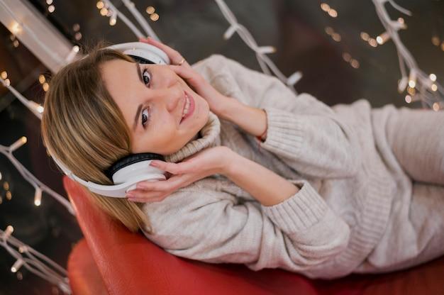 Mulher sorridente segurando fones de ouvido na cabeça e sentado no sofá perto de luzes de natal
