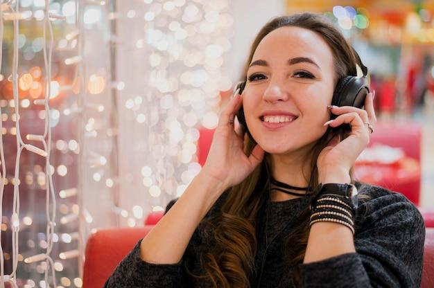 Mulher sorridente segurando fones de ouvido na cabeça perto de luzes de natal