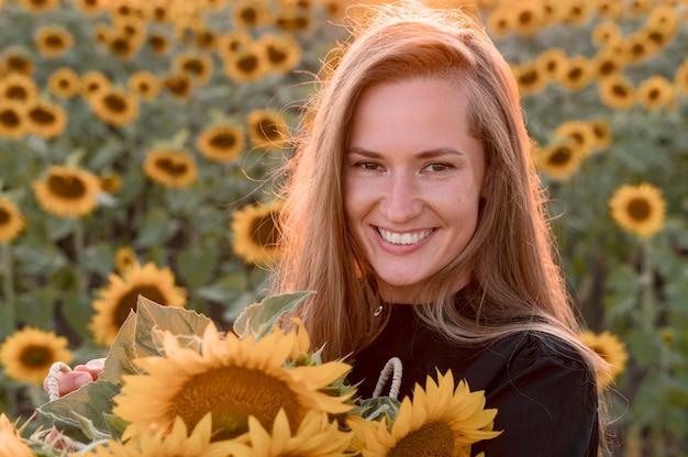Mulher sorridente segurando girassóis