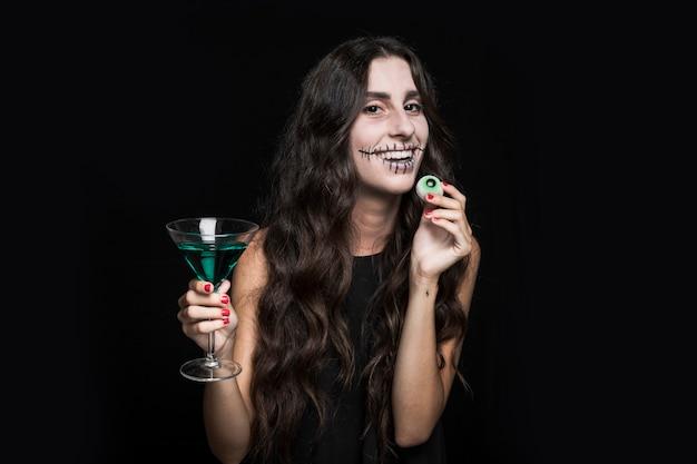 Mulher sorridente, segurando, goblet, com, turquesa, líquido, e, olho falso
