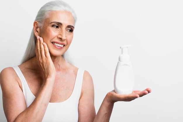 Mulher sorridente segurando hidratante