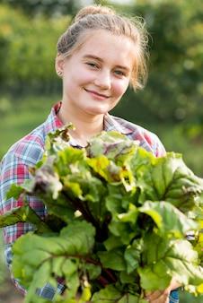 Mulher sorridente segurando legumes