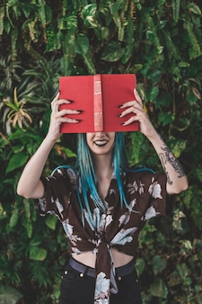 Mulher sorridente, segurando, livro vermelho, frente, dela, olhos
