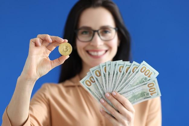 Mulher sorridente segurando moeda bitcoin e notas de dólar americano nas mãos, close up