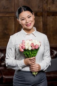 Mulher sorridente segurando o buquê de flores