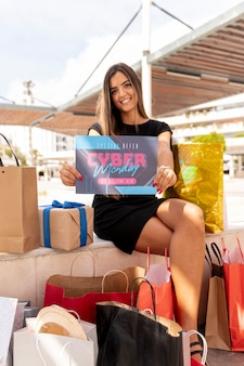 Mulher sorridente, segurando o cartão promocional