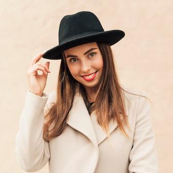 Mulher sorridente segurando o chapéu