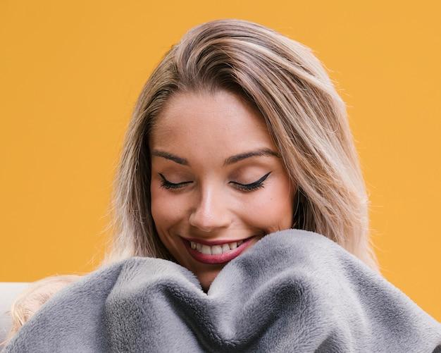 Mulher sorridente segurando o cobertor com os olhos fechados em casa