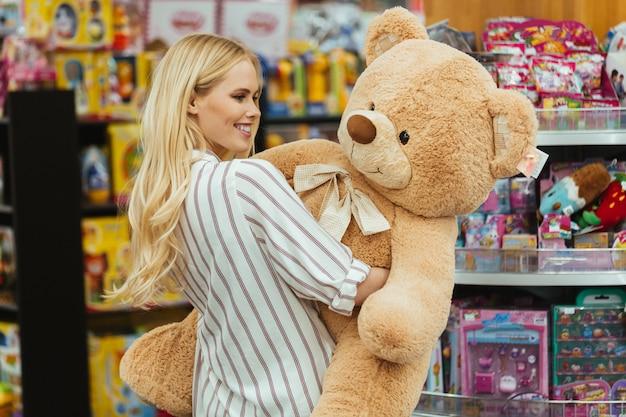 Mulher sorridente segurando o grande urso de pelúcia