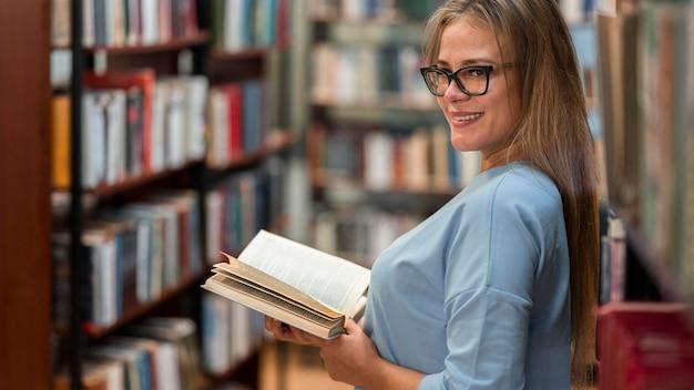 Mulher sorridente segurando o livro de lado
