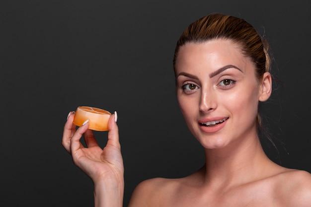 Mulher sorridente segurando o produto de cuidados da pele