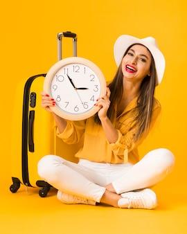 Mulher sorridente segurando o relógio e posando ao lado de bagagem