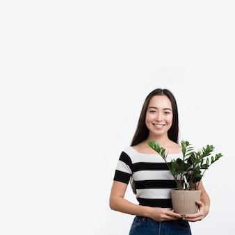 Mulher sorridente segurando o vaso de flores