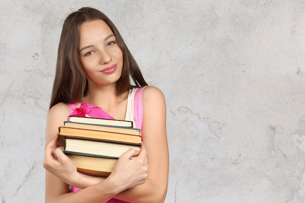 Mulher sorridente, segurando, pilha livros