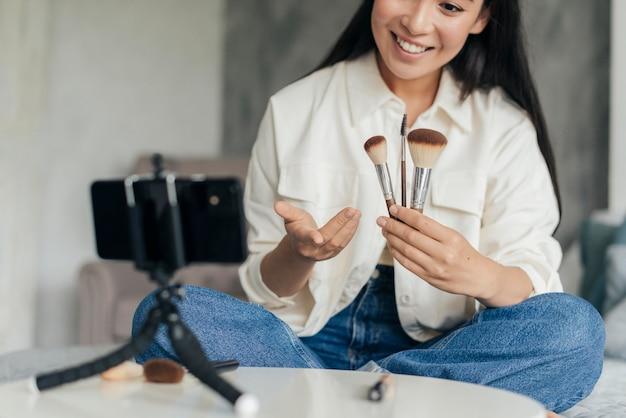 Mulher sorridente segurando pincéis de maquiagem enquanto faz o vlog