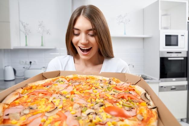 Mulher sorridente segurando pizza quente na caixa em casa