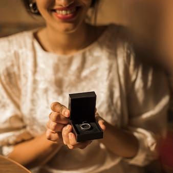 Mulher sorridente, segurando, presente, caixa, com, anel