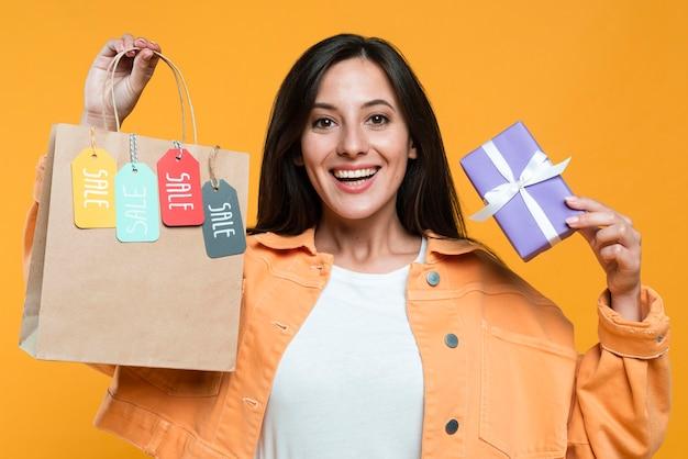 Mulher sorridente segurando sacola de compras com etiquetas e cartão de crédito