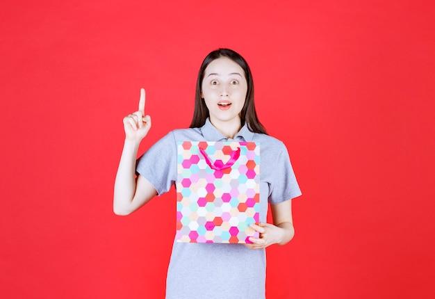 Mulher sorridente segurando sacola de compras e apontando o dedo para cima