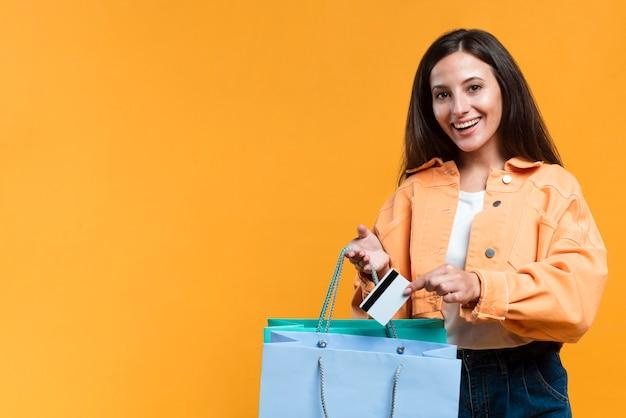 Mulher sorridente segurando sacola de compras e cartão de crédito com espaço de cópia