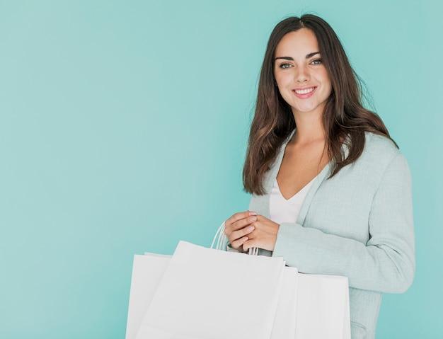 Mulher sorridente segurando sacolas brancas