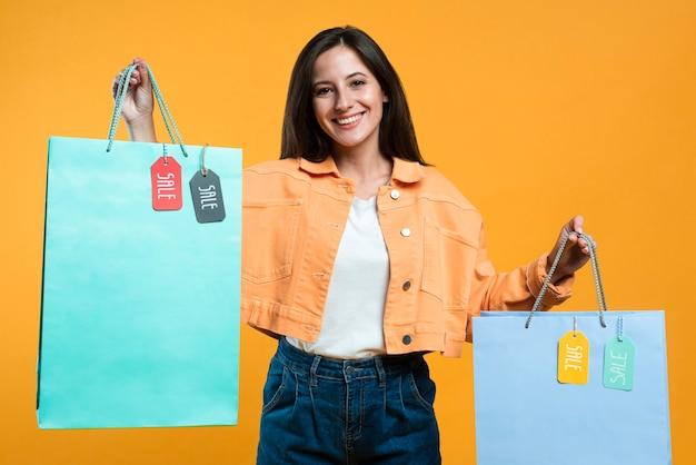 Mulher sorridente segurando sacolas de compras com etiquetas