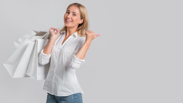 Mulher sorridente segurando sacolas de compras e apontando para uma possível venda na loja