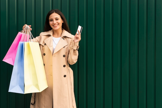 Mulher sorridente segurando sacolas de compras e cartão de crédito com espaço de cópia