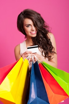Mulher sorridente segurando sacolas de compras e cartão de crédito