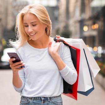 Mulher sorridente segurando sacolas de compras e olhando para o smartphone