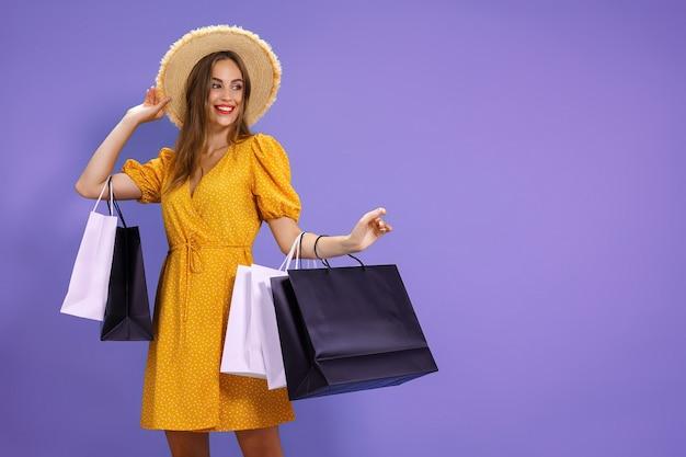Mulher sorridente segurando sacolas de compras em fundo colorido salepurchases compras preto sexta-feira