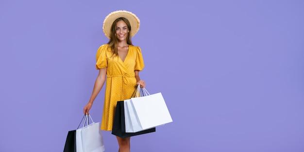 Mulher sorridente segurando sacolas de compras sobre fundo roxo.