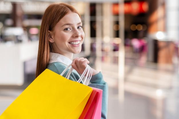 Mulher sorridente segurando sacolas de compras
