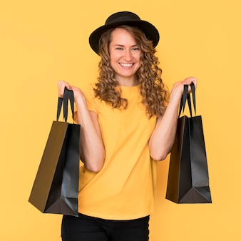 Mulher sorridente segurando sacolas pretas de compras na sexta-feira