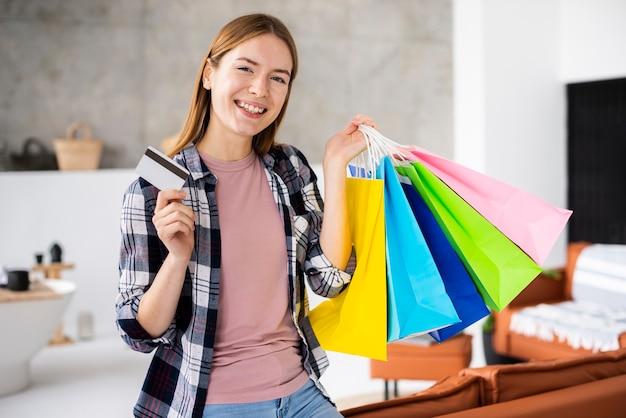 Mulher sorridente segurando sacos de papel e cartão de crédito