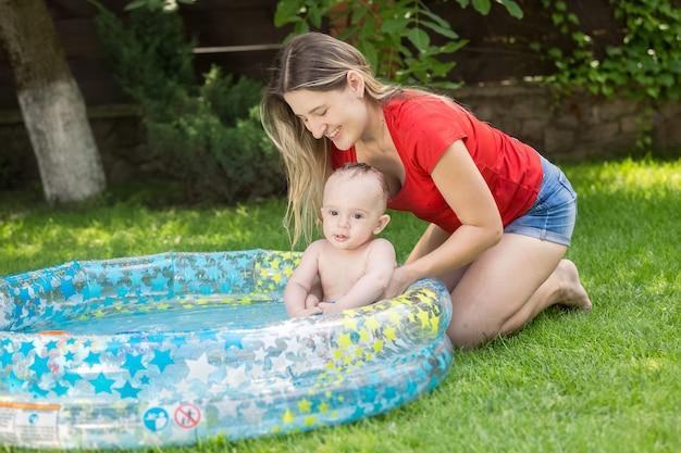Mulher sorridente segurando seu filho na piscina inflável do jardim