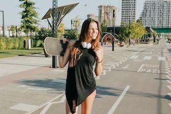 Mulher sorridente, segurando, skateboard, ficar, ligado, rua