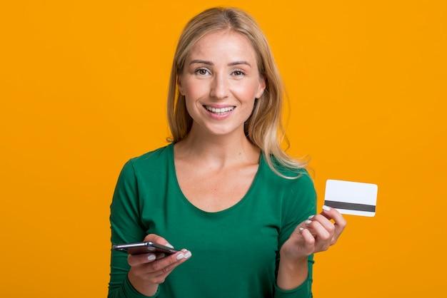 Mulher sorridente segurando smartphone e cartão de crédito