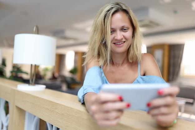 Mulher sorridente segurando smartphone e olhando para a correspondência na tela e o conceito de visualização de correspondência