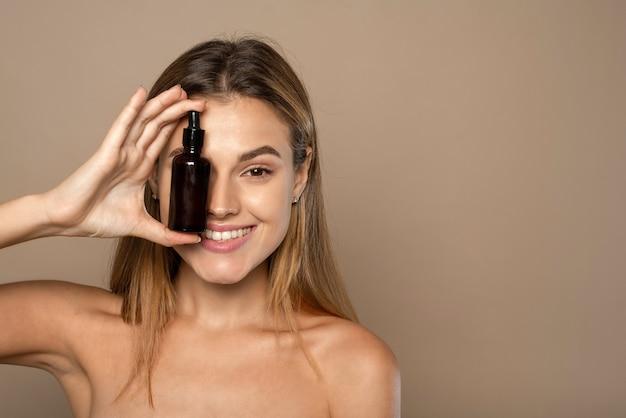 Mulher sorridente segurando soro de vitamina c perto de seu rosto em fundo bege. conceito de cuidados com a pele e saúde.
