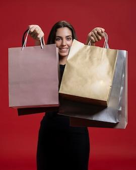 Mulher sorridente segurando suas sacolas de compras