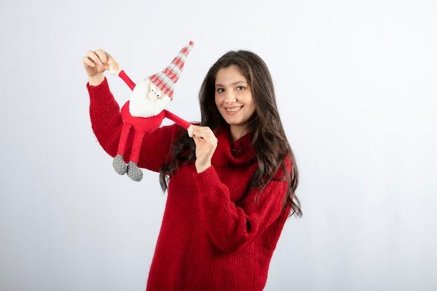 Mulher sorridente segurando um brinquedo de papai noel nas mãos. .