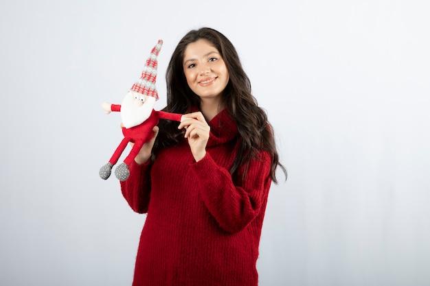 Mulher sorridente segurando um brinquedo de pelúcia do papai noel nas mãos.