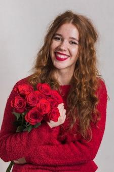 Mulher sorridente segurando um buquê de rosas