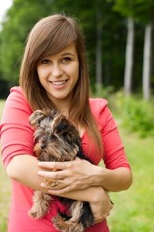 Mulher sorridente segurando um cachorrinho fofo