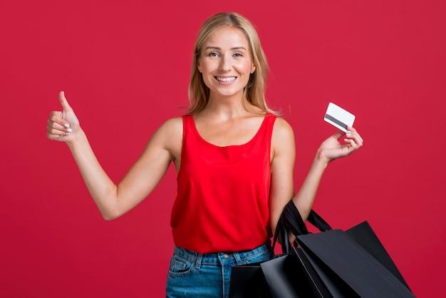Mulher sorridente segurando um cartão de crédito e sacolas de compras enquanto faz sinal de positivo