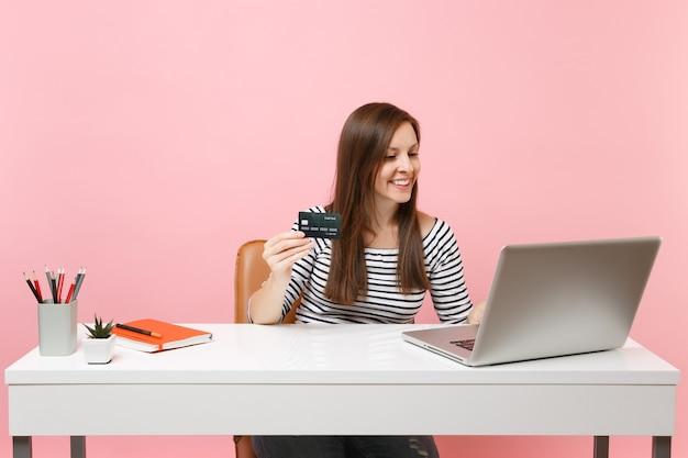 Mulher sorridente segurando um cartão de crédito enquanto trabalha em um projeto enquanto está sentado no escritório com o laptop