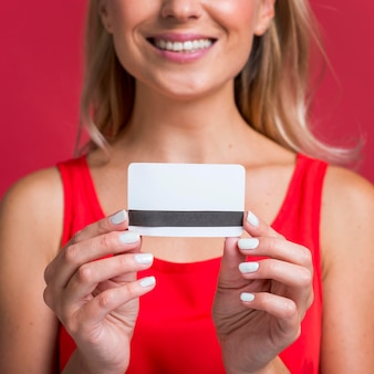 Mulher sorridente segurando um cartão de crédito