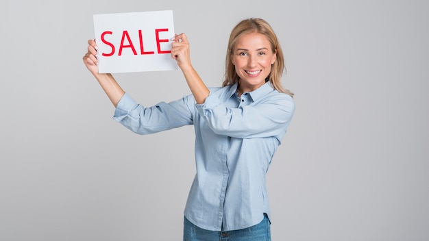 Mulher sorridente segurando um cartaz de venda